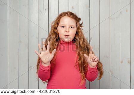 Portrait Of Cute Redhead Preteen Girl 7-9 Years Old Showing Seven Fingers. Studio Shot, Light Wooden