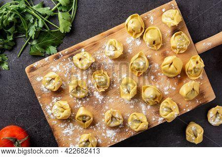 Uncooked Pelmeni Dumplings On Black Background. Top View