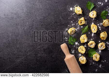 Uncooked Pelmeni Dumplings On Black Background. Top View. Copy Space