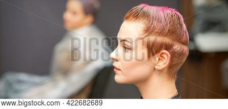 Young Caucasian Woman With Pink Hair Getting A Short Haircut By A Male Hairdresser\'s Hands In A Hai