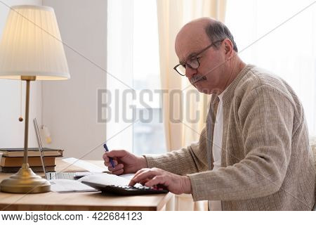 Senior Man Sitting With Paperwork And Using Calculator While Counting Money