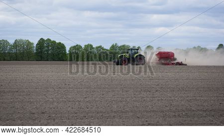 Tractor In A Field Side View, Tractor Planting Crops On An Agricultural Field. Big Green Tractor Wor
