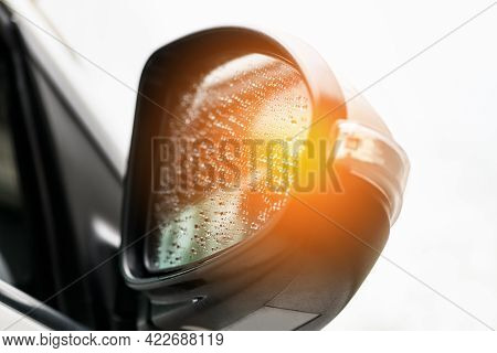 Car Side Mirror With Water Droplets With Tempered Light. Selective Focus