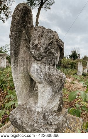 Close Up View Of Broken Weathered Tombstone With Stone Angel On Old Abandoned City Or Village Cemete