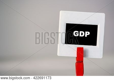 Plastic Frame With Clothes Pin On Table. White Frame With Black Background And Inscription Word Gdp.