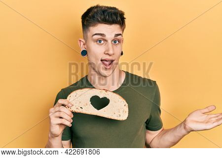 Young caucasian boy with ears dilation holding bread loaf with heart shape celebrating achievement with happy smile and winner expression with raised hand