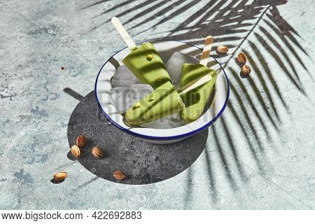 Frozen Homemade Pistachio Popsicle In Bowl Of Ice On Gray Background With Palm Leaf Shadow In Harsh