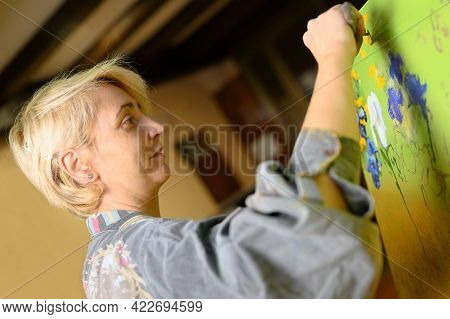 Cinematic Shot Of Female Creative Artist Painter Concentrated And Inspired Painting Picture With Pai