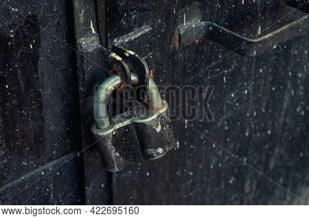 Retro Padlock On An Old Iron Black Door To The Basement Of A Building. The Entrance Is Closed Behind