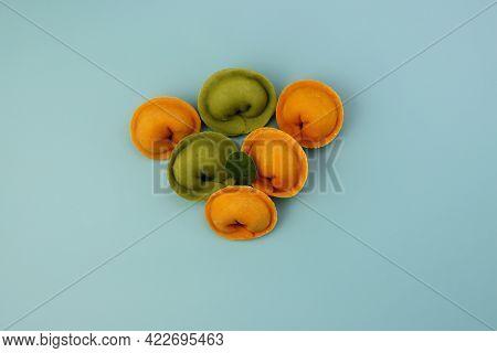 Yellow And Green Dumplings On A Blue Background. Raw Homemade Dumplings.