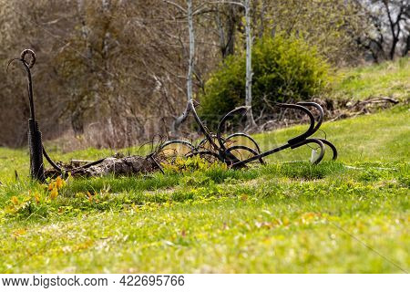 Metal Anchor, Boat Tie Up Ring And Other Fishing Equipment Is Laying In Grass Near River During Spri