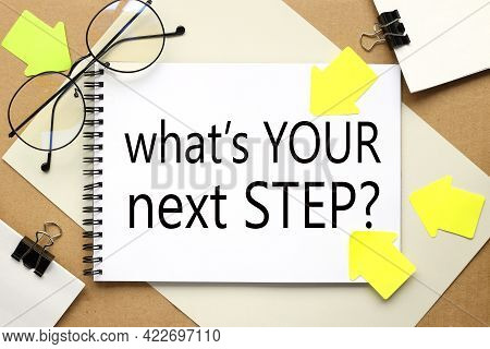 What's Your Next Step. Inscription On A Notebook On A Craft And Gray Background
