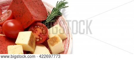Dutch red cheese with tomatoes on a white plate. Cheddar cheese