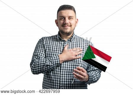 White Guy Holding A Flag Of Sudan And Holds His Hand On His Heart Isolated On A White Background Wit