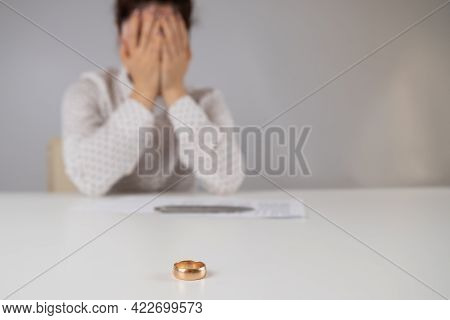 Widow Mourns The Death Of Her Husband. Caucasian Woman Signs Divorce Papers And Cries