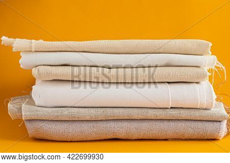 Natural Fabrics Stacked In Pile Lie On A Yellow Background