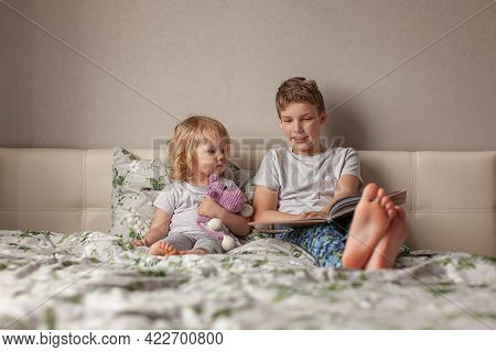 Home Little Blonde Girl In Pajamas Sitting On Bed, Hugging Her Favorite Knitted Toy, Teenage Boy Sit