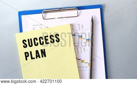 Success Plan Text Written On Notepad With Pencil. Notepad On A Folder With Diagrams. Financial Conce