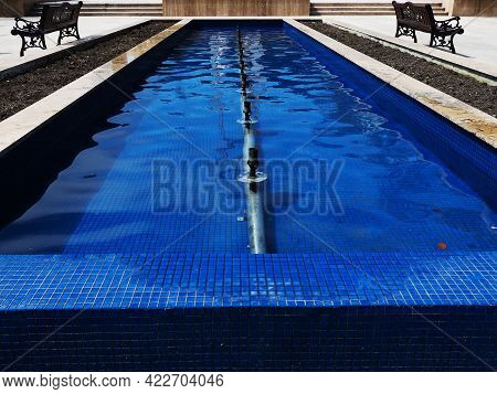 A Blue Pool With Water And An Iron Pipe For A Fountain In It In The Park On A Sunny Day. Not Working