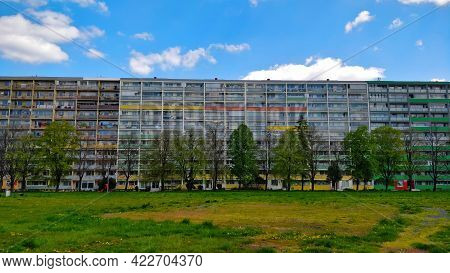 Old Communist Style Block Of Flats With Trees In Front Of Them And Large Grassland. The Weather Is B