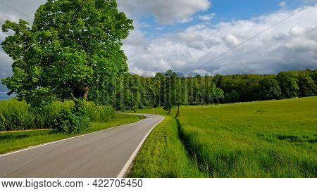 Road Going Through South Bohemian Countryside During Beautiful Spring Weather. There Is A Grassland