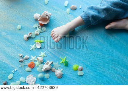 Baby Feet On Seashells Summer Background. Many Different Seashells, Starfish On A Background Of Blue