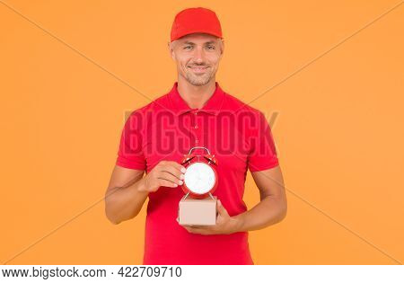 Postman Delivery Worker. Handsome Man Red Cap Hold Alarm Clock Yellow Background. Delivering Purchas