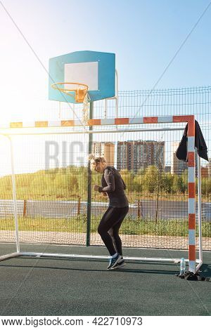 Outdoor Training. Sportswoman In Black Tight Tracksuit Workout On The Playground In The Morning. Fit
