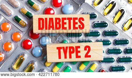 Against The Background Of Multi-colored Plates, Wooden Blocks With The Text Diabetes Type 2. Medical