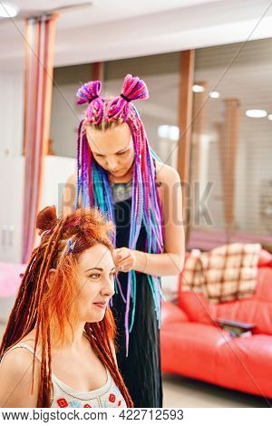 Girl Hairdresser With Colored Afro Braids Weaves To Female Ginger Dreadlocks. Weaving Process With K