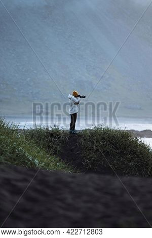 Photographer on a green hill at the Stokksnes peninsula in Southeast Iceland