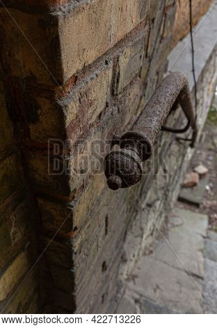 Old Ornate Forged Railing At An Brick Wall. Rusty Metal Railing On A Abandoned Historic House. Iron