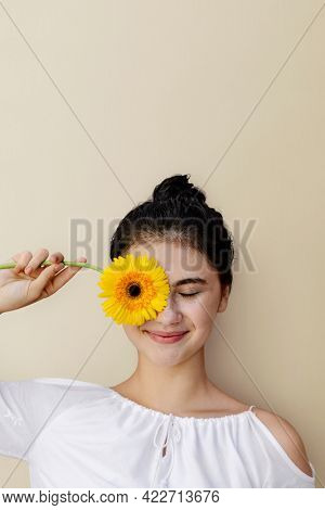 Beautiful young girl with a yellow gerbera flower