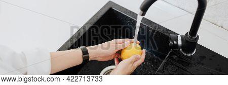 Woman rinsing a yellow lemon in a sink