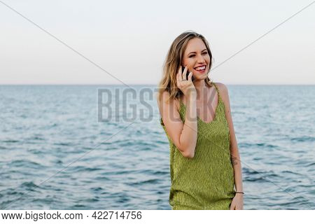 Woman in a green dress talking on her phone at the beach