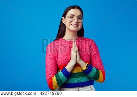 Smiling Young Attractive Girl Show Praying Gesture, Wears Rainbow Sweater
