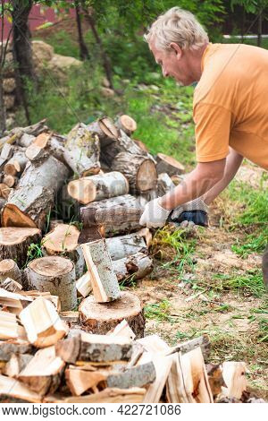 A Man Chops Wood With A Large Ax In The Yard Of His House. Procurement Of Fuel For The Winter For He