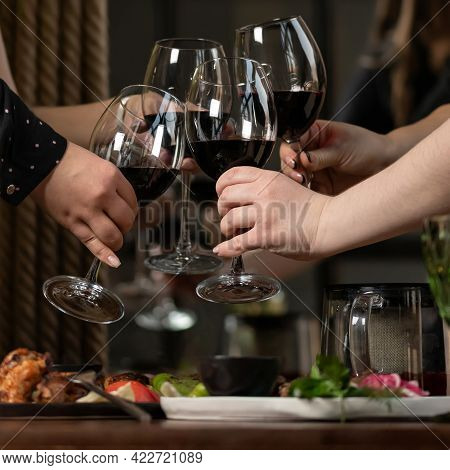 Cheering Toast. Four Women Clinking With Red Wine Glasses. Female Group Have Dinner Together And Dri