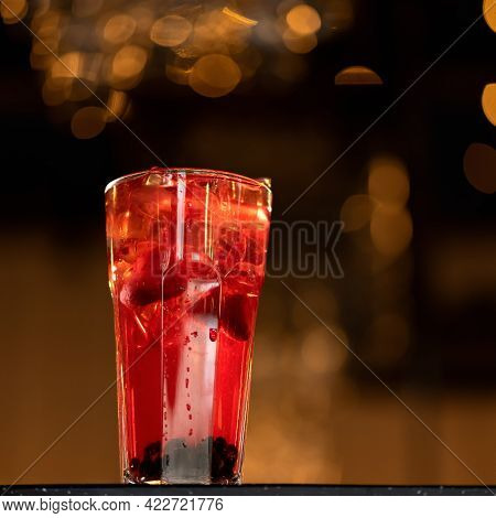Glass Of Clear Red Berry Drink With Ice Cubes Backlit On Dark Blurred Background With Bokeh. Alcohol