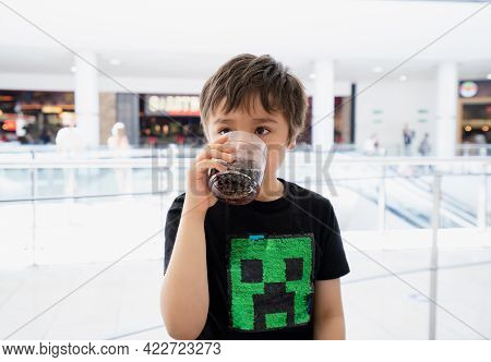 Kid Drinking Cold Soda, Happy Child Sitting In Cafe Drinking Soft Drink From Glass, Sitting In Cafe