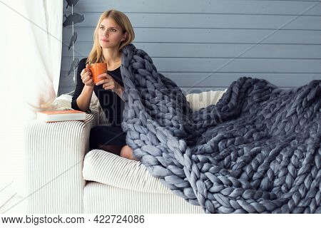 A Woman In A Black Jumper Holds A Cup Of Tea And Looks Out The Window, Covered By A Green Merino Bla