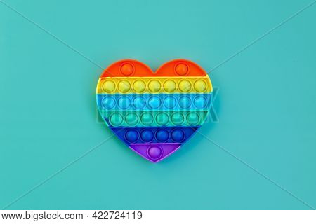 Top view of colorful markers and anti stress sensory toy pop it rainbow heart on green background cl