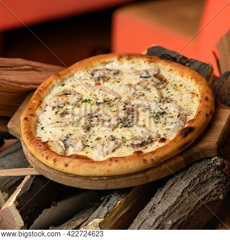 Hot Whole Pizza On Wood With Crispy Brown Crust And Filling Of Chicken Fillet And . Open Fire On Blu