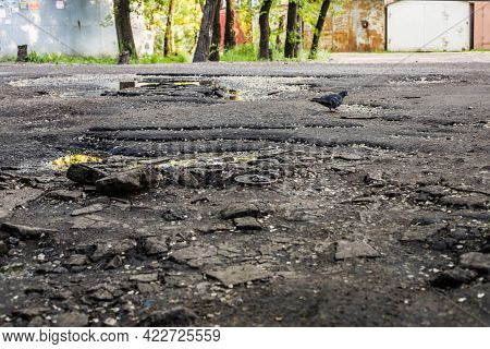 Asphalt Roads In Damaged Condition With Holes In Cracks And Bumps Are Dangerous For Road Users. Dama