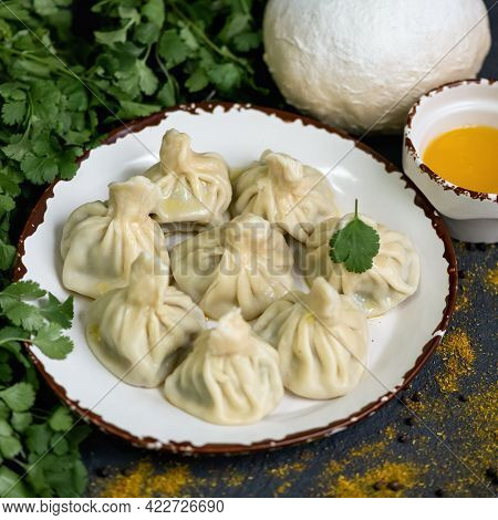 Plate With Cooked Boiled Dumplings Or Khinkali Surrounded By Parsley And Ingredients For Cooking Pro