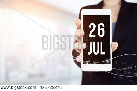 July 26th. Day 26 Of Month, Calendar Date. White Smartphone With Calendar Date In Businesswoman Hand