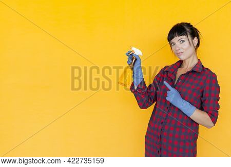 Female Hand In Blue Protective Glove Holding Yellow Spray Bottle, Hand Point Finger To Copy Space. H