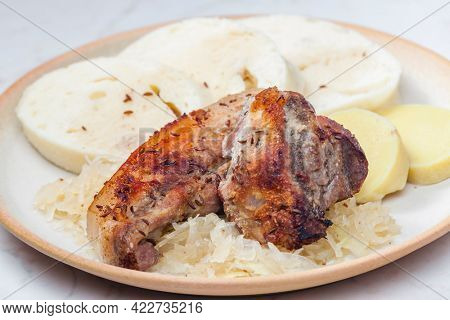 pork meat on cumin with cabbage and dumplings
