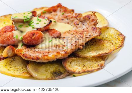 roasted pork meat with sausage, mustard sauce and roasted potatoes