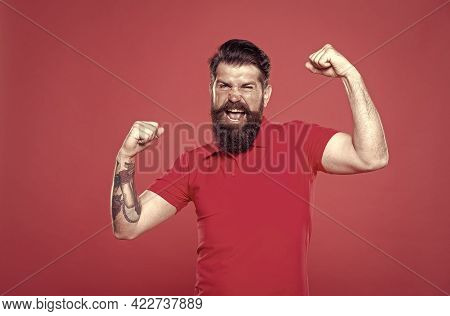 Strength And Drive. Bearded Man Show Strength. Strong Hipster Flex Arms Red Background. Strength And